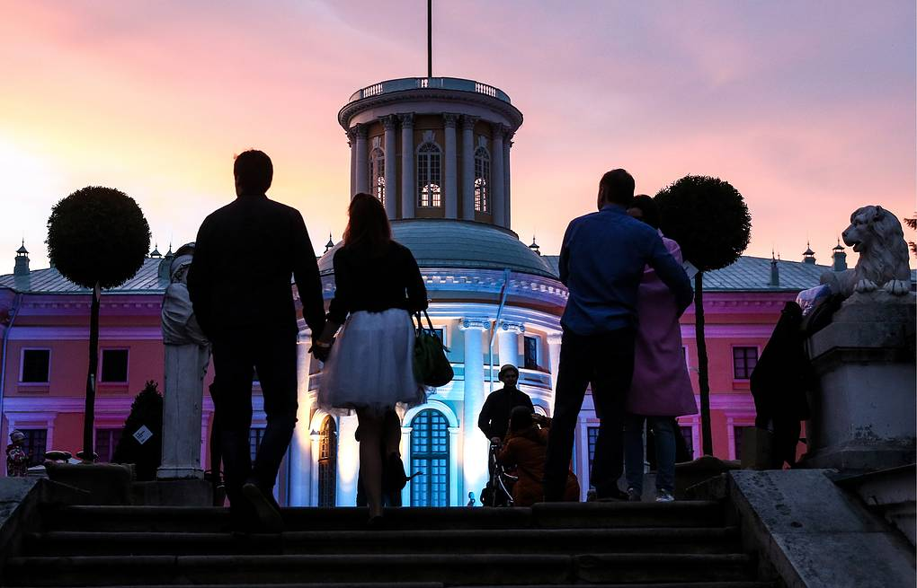 Visitors walk outside a lit mansion at Usadba Jazz International Festival in Arkhangelskoye Estate Valery Sharifulin/TASS