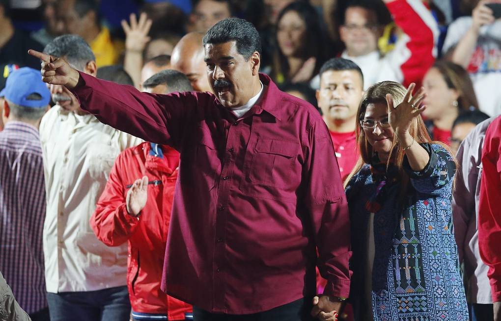 Venezuela's President Nicolas Maduro and his wife Cilia Flores wave to supporters at the presidential palace in Caracas AP Photo/Ariana Cubillos