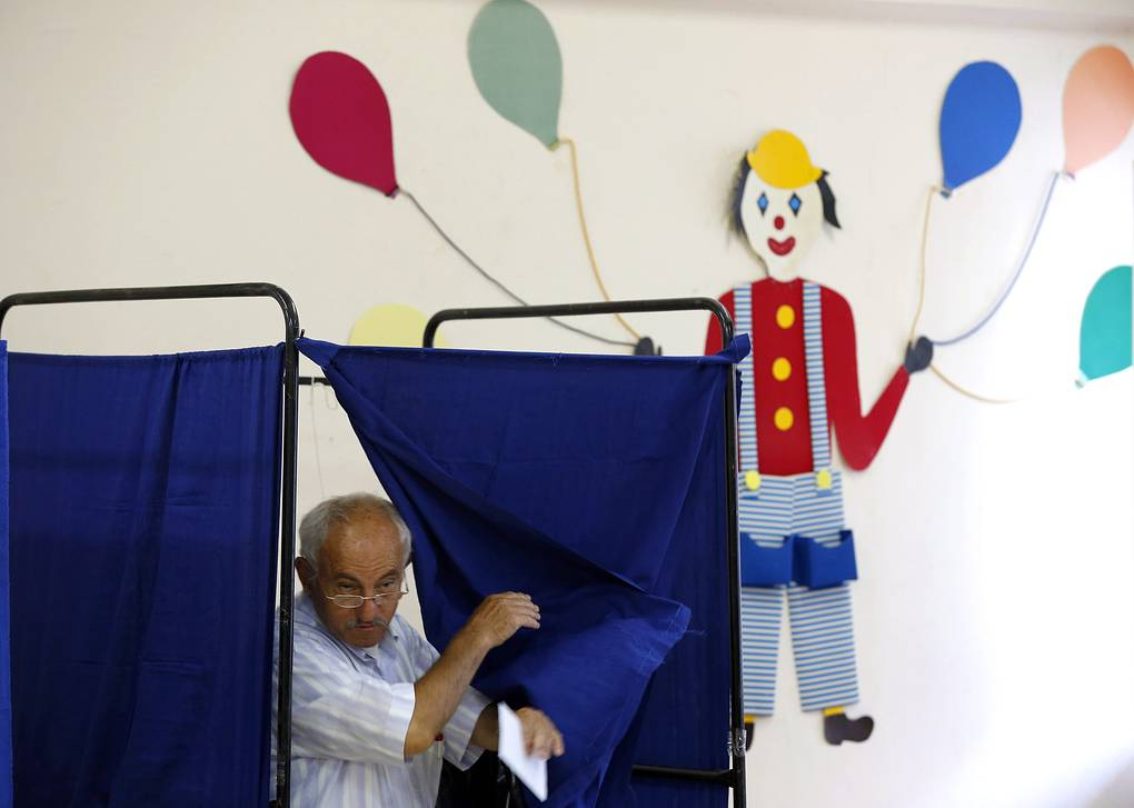 A man comes out of a voting booth during a referendum voting in Athens, Greece, 05 July 2015. Greece is voting on 05 July 2015, on its bailout conditions in a snap referendum with far-reaching consequences for the debt-laden country and the rest of Europe. With banks shuttered all week, cash withdrawals capped and businesses already feeling the strain of capital controls, the ballot could decide whether Greece gets another financial rescue in exchange for more harsh austerity measures - or plunges deeper into crisis. The vote may not only determine Greece's economic fate but also serve as a nationwide vote of confidence in Alexis Tsipras' government, which came to power in January on an anti-austerity ticket. EPA/ARMANDO BABANI