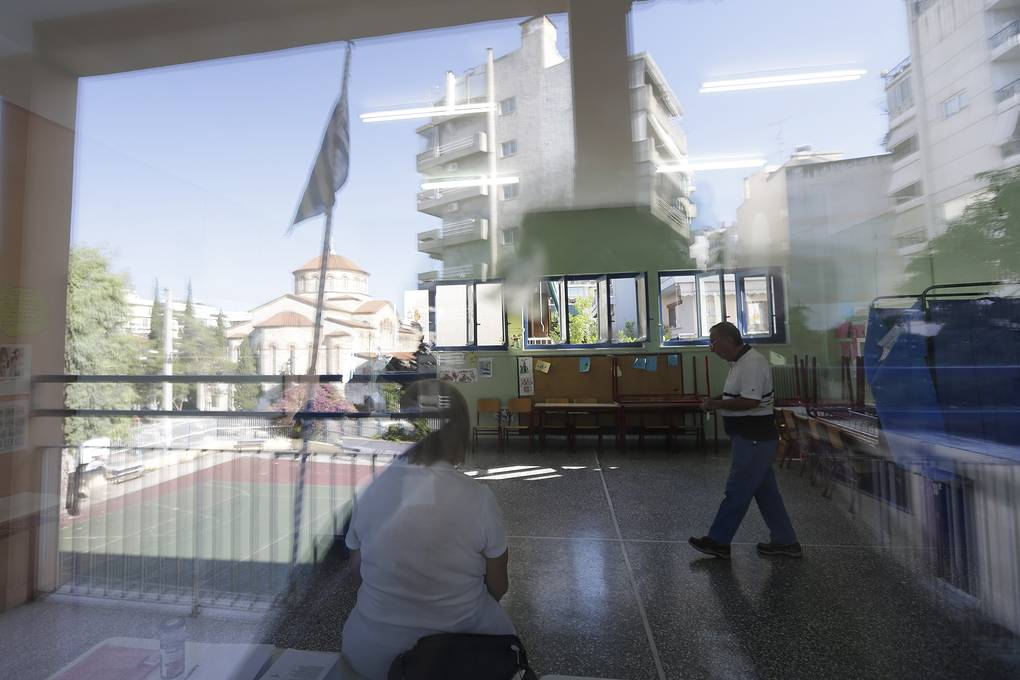 People are reflected on a window as they cast their vote at a polling station next to a Greek Orthodox church in Athens, Sunday, July 5, 2015. Greeks began voting early Sunday in a closely-watched, closely-contested referendum, which the government pits as a choice over whether to defy the country's creditors and push for better repayment terms or essentially accept their terms, but which the opposition and many of the creditors paint as a choice between staying in the euro or leaving it. (AP Photo/Petr David Josek)