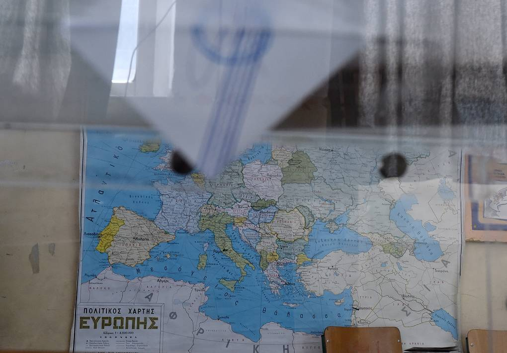 A man casts his vote as the map of Europe is seen in the background in the northern port city of Thessaloniki, Sunday, July 5, 2015. Greeks were voting Sunday in a bailout referendum that will decide the country's future, with opinion polls showing people evenly split on whether to accept creditors' proposals for more austerity in exchange for rescue loans or defiantly reject the deal. (AP Photo/Giannis Papanikos)