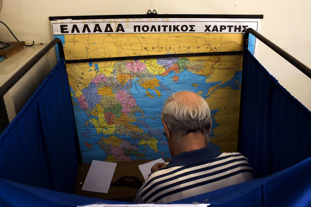 A man fills his ballot paper next to a Greek political map before casting his vote at a polling station in Athens, Sunday, July 5, 2015. Greeks were voting Sunday in a critical bailout referendum, with opinion polls showing people evenly split on whether to accept creditors' proposals for more austerity in exchange for rescue loans, or defiantly reject the deal. (AP Photo/Emilio Morenatti)