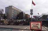 "Barricades and Soviet era red and Russian national flags with a poster reading "" Stop, no entrance! "" in front of the Ukrainian regional office of the Security Service in Luhansk"