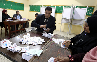 Egyptian election officials count ballots after voting in the second day of a referendum on the new constitution