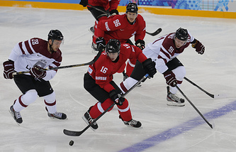 Raphael Diaz (C) of Switzerland fights for the puck with Latvia players Zemgus Girgensons (L) and Ronalds Kenins (R)
