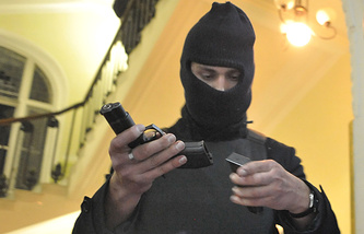 A protester examines a pistol in the seized regional Interior Ministry department in the west-Ukrainian city of Lviv Feb. 19 2014