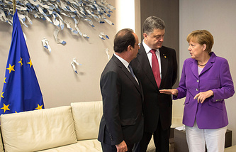 German Chancellor Angela Merkel, French President Francois Hollande (L) and Ukrainian President Petro Poroshenko (C) talking after signing the agreement for closer ties between the EU and Ukraine