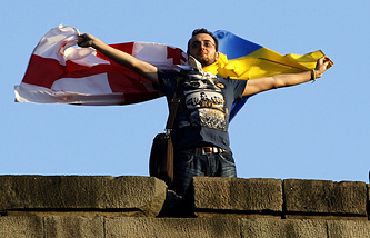 A man holds Ukrainian and Georgian national flags at a concert marking the signing of the association with EU agreement