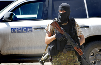 A militiaman guards OSCE mission vehicles in eastern Ukraine
