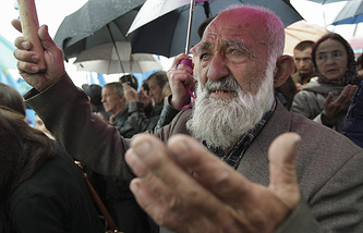 Crimean Tatars seen praying during a commemoration ceremony
