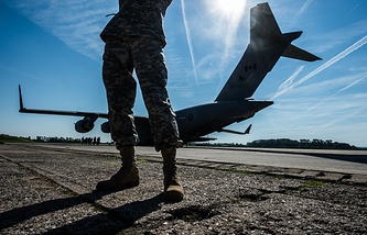 A US soldier stands in front of a Canadian cargo plane