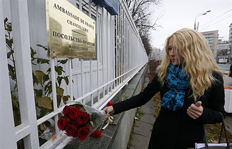 A woman lays flowers at the wall of France's embassy in Moscow