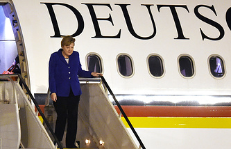 German Chancellor Angela Merkel unboards an aircraft as she arrives in Brisbane