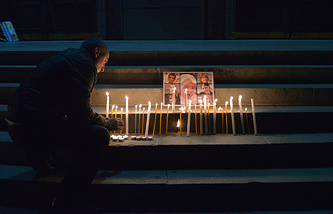 Armenian man lights candles in memory of a 6-month-old baby and his family slain in Gyumri