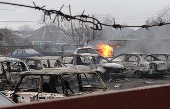 Burnt out vehicles in a street in Mariupol, Ukraine