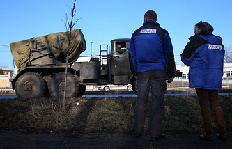 OSCE observers watch a multiple launcher being pulled back in eastern Ukraine, Feb.27