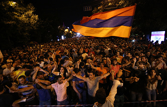 Armenian protesters dance while waving a national flag during a protest rally against a hike in electricity prices in Yerevan, Armenia, Wednesday, June 24, 2015