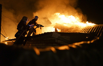 Firefighters extinguishing fire at a house destroyed by night-long shelling in Donetsk, eastern Ukraine