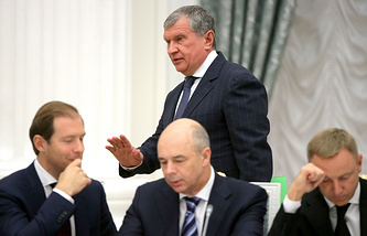 Rosneft CEO Igor Sechin (background), Russia's Industry and Trade Minister Denis Manturov, Russia's Finance Minister Anton Siluanov and Russia's Science and Education Minister Dmitry Livanov