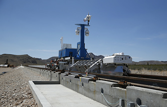 Recovery vehicle and test sled sit on a track after a test of a Hyperloop One propulsion system