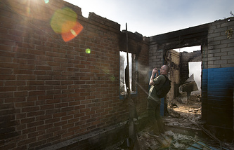 Journalist filming a destroyed house in Semyonovka village, Ukraine