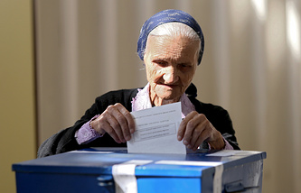 A woman casts her ballot in a referendum over a disputed national holiday in the Bosnian Serb town of Banja Luka