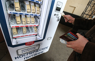 A man inserts money in a vending machine in Moscow to buy space food in tubes that is used by austronauts in space