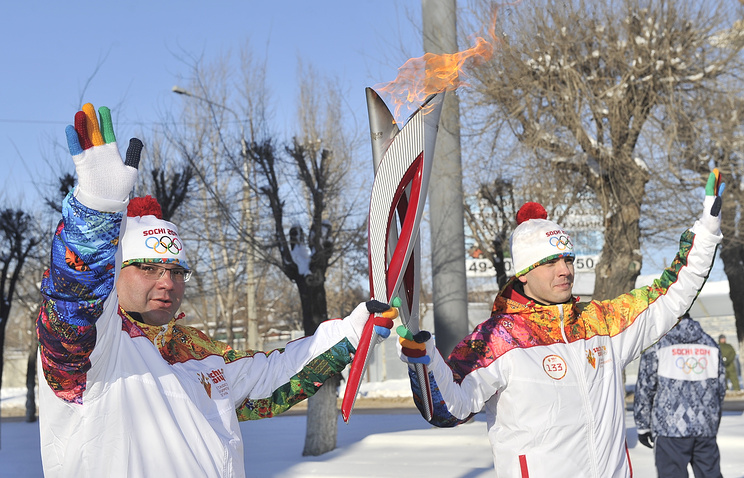ITAR-TASS News Agency general director Sergei Mikhailov (L) holds a torch with Olympic Flame on Day 105 of the Sochi 2014 Olympic Torch Relay