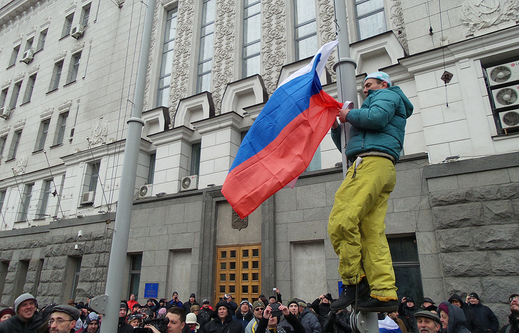 A protester in Ukraine's Kharkiv is hoisting a Russian flag