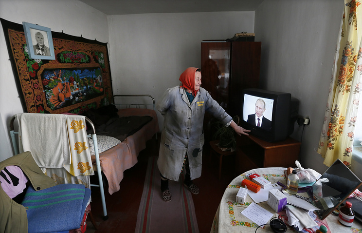 A woman in Crimea turns on a television set to watch Russian President Vladimir Putin addressing the Russian Federal Assembly