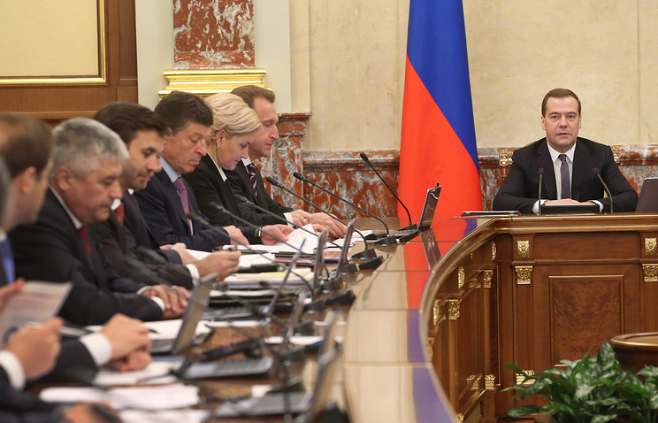 Dmitry Medvedev (R) holding a government meeting Mar. 27