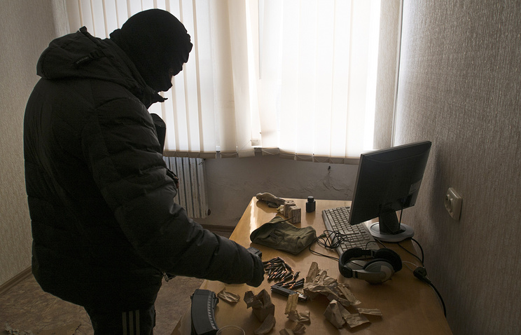 A masked man inside the regional department of Ukraine's Security Council in Luhansk