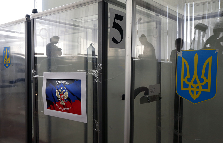 Ukrainian coat-of-arms (R) and the flag of the self=proclaimed Donetsk People's Republic (L) seen on ballot boxes at the referendum