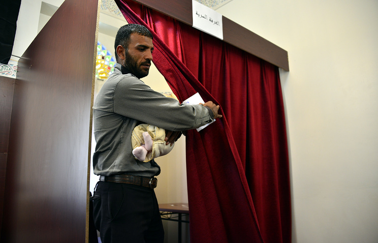 A Syrian man living in Yemen carrying his baby leaves a polling booth during the Syrian presidential elections at a polling station set up in the Syrian embassy in Sana'a, Yemen, May 28, 2014