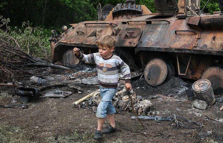 A child near a destroyed APC in east Ukraine