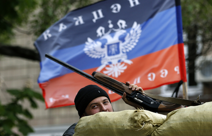A militia fighter and Donetsk People's Republic flag seen in Sloviansk