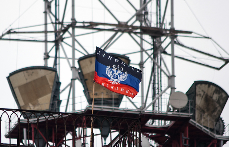 A flag of Donetsk People's Republic waves on a roof of the regional TV center in Donetsk
