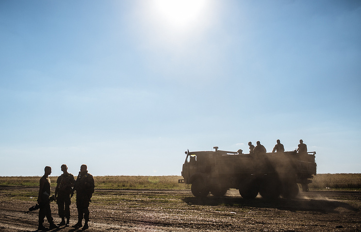 Ukrainian soldiers drive on a truck close to their military camp near Luhansk