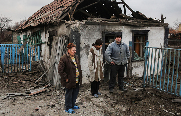 Local residents outside a house destroyed during an artillery attack in Donetsk