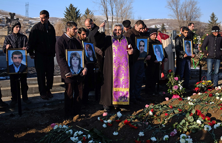 People hold portraits of six dead members of the Avetisyan family during a funeral in the city of Gyumri, Armenia