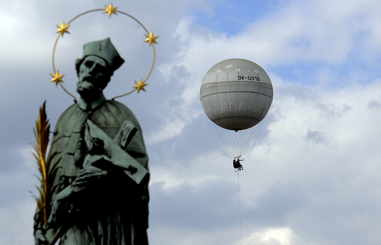 An air balloon rented by tourists seen next to a statue of John of Nepomuk on the medieval Charles Bridge in Prague