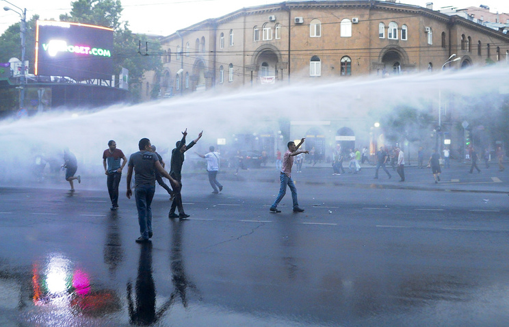 Armenian police use a water cannon to disperse protesters demonstrating against an increase in electricity prices in the Armenian capital of Yerevan, Tuesday, June 23, 2015