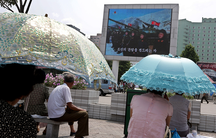 People watching a movie showing soldiers line up in front of their tanks shown on a large screen in Pyongyang, North Korea