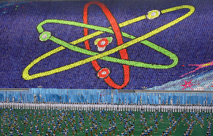 Thousands of North Koreans turn colored cards to form the symbol for the atom