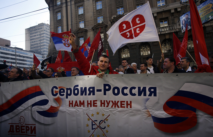 "Protesters holding a banner that reads: ""Serbia - Russia, we don't need European Commission"" in front of the government building in Belgrade, March 21, 2015"
