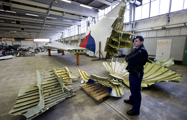 Dutch military police standing next to parts of the wreckage of the Malaysia Airlines Flight MH17, in a hangar at Gilze-Rijen airbase, Netherlands