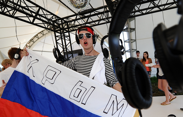A young man holding a Russian flag with the word 'Crimea' written on it
