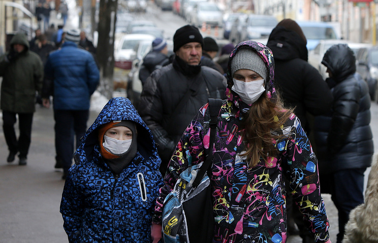 People wearing face masks walking in a street in Kiev, Ukraine