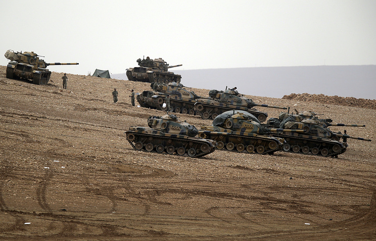 Turkish soldiers hold their positions with their tanks on a hilltop on the outskirts of Suruc, at the Turkey-Syria border, December 2014