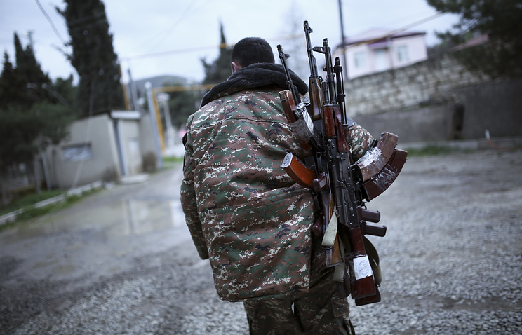 Armenian fighter with Kalashnikov machine guns in the region of Nagorno-Karabakh